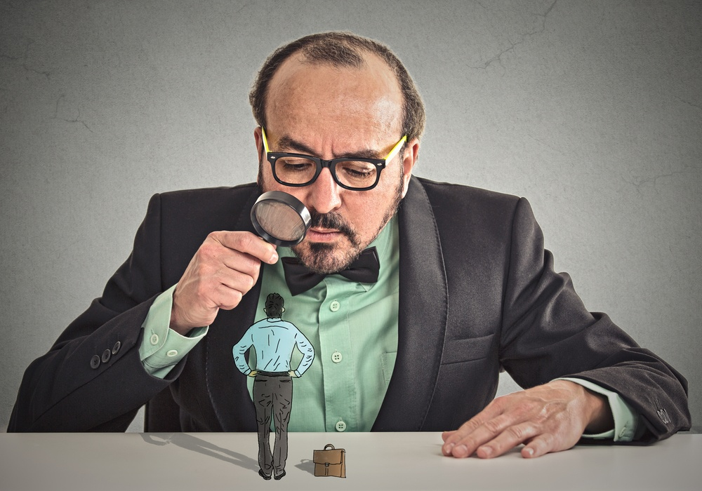 Curious corporate businessman skeptically meeting looking at small employee standing on table through magnifying glass isolated office grey wall background. Human face expression, attitude, perception