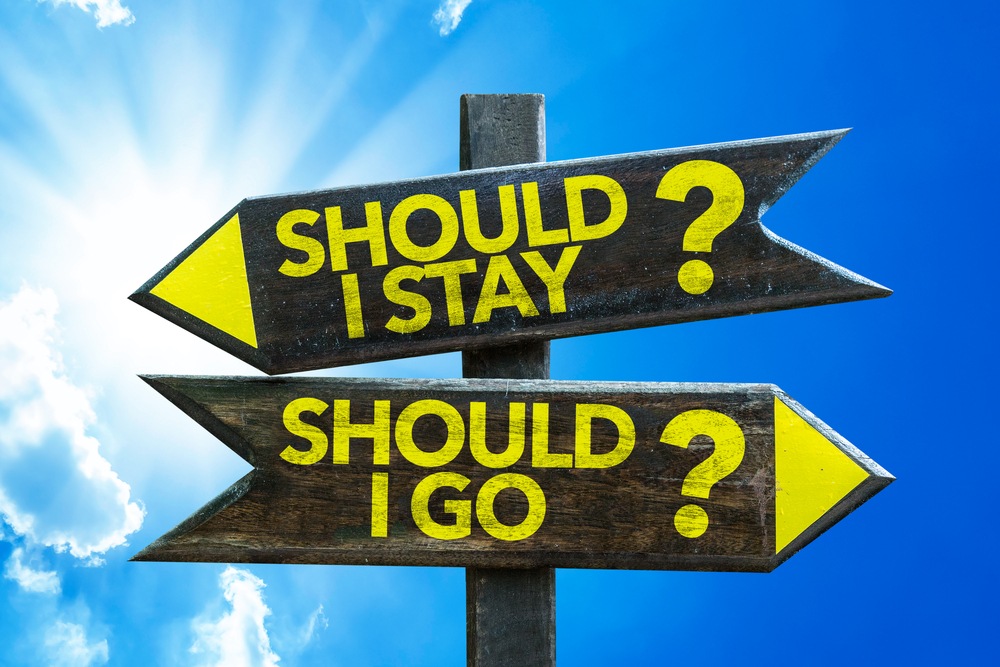Should I Stay? Should I Go? signpost with sky background